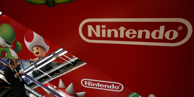 """File photo: A shopper rides the escalator past Nintendo advertisements at an electronics retail store in Tokyo January 20, 2014. Shares in Nintendo Co Ltd tumbled by nearly a fifth on Monday after it warned of a third straight year of operating losses, heaping pressure on the creator of """"Super Mario"""" to abandon its policy of not licensing its software to rivals. (REUTERS/Yuya Shino)"""