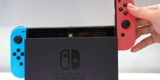 A model puts the controller on to the Nintendo Switch during a presentation event of the new Nintendo Switch in Tokyo, Friday, Jan. 13, 2017. (AP Photo/Koji Sasahara)