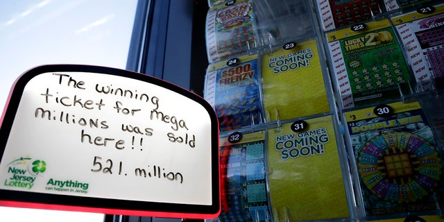A sign is displayed near scratch-off tickets inside a Lukoil service station where the winning ticket for the Mega Millions lottery drawing was sold, Saturday, March 31, 2018, in Riverdale, N.J.
