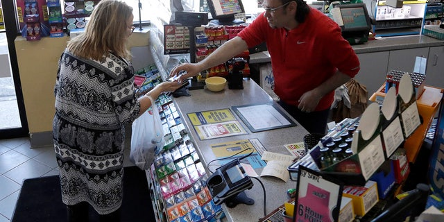 A cashier checks out a customer at a Lukoil service station where the winning ticket for the Mega Millions lottery drawing was sold, Saturday, March 31, 2018, in Riverdale, N.J.