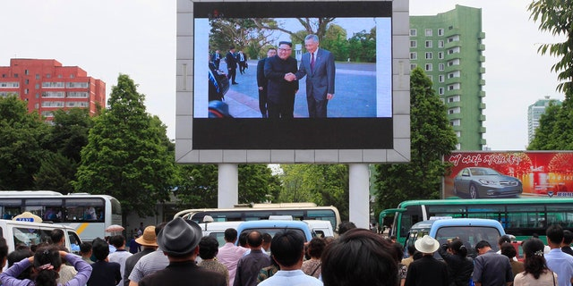 People watch a large screen at the main train station airing video of North Korean leader Kim Jong Un shaking hands with Singapore Prime Minister Lee Hsien Loong during his trip to Singapore in Pyongyang.