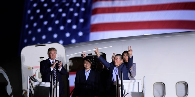 President Donald Trump, from left, greets Tony Kim, Kim Hak Song, seen in the shadow, and Kim Dong Chul, three Americans detained in North Korea for more than a year, as they arrive at Andrews Air Force Base in Md., Thursday, May 10, 2018. First lady Melania Trump is seen at right.