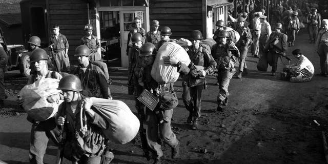 American foot soldiers leave the railroad station at Taejon, South Korea, en route to the battle front against North Korea.