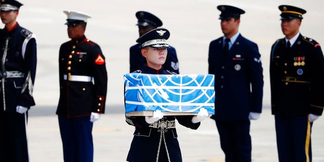 A soldier carries a casket containing a remain of a U.S. soldier who was killed in the Korean War during a ceremony at Osan Air Base in Pyeongtaek, South Korea, Friday, July 27, 2018.  The U.N. Command said the 55 cases of war remains retrieved from North Korea will be honored at a ceremony next Wednesday at a base in South Korea. (Kim Hong-Ji/Pool Photo via AP)