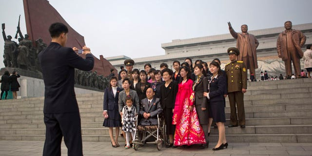 Apr. 15, 2014: A North Korean family poses for a souvenir photograph in front of bronze statues of the late leaders Kim Il Sung and Kim Jong Il at Munsu Hill in Pyongyang on the official birthday of Kim Il Sung.