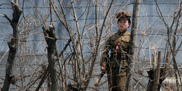 A North Korean prison policewoman stands guard behind fences at a jail on the banks of Yalu River near the Chongsong county of North Korea, opposite the Chinese border city of Dandong. Many Christians in North Korea are sent to prison camps where they are tortured for their faith.