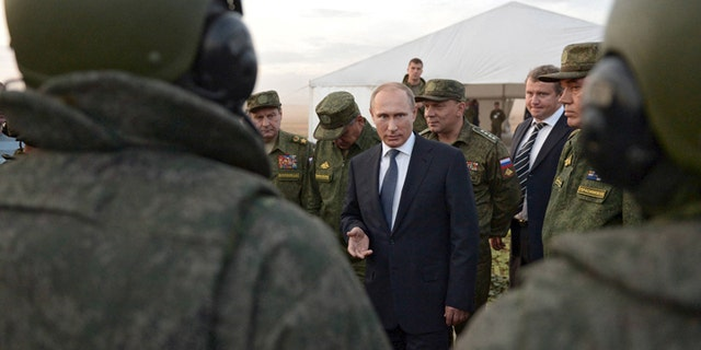 Russian President Vladimir Putin (C) talks to servicemen during a training exercise at the Donguz testing range in Orenburg region, Russia, September 19, 2015.  REUTERS/Alexei Nikolsky/RIA Novosti/Pool ATTENTION EDITORS - THIS IMAGE HAS BEEN SUPPLIED BY A THIRD PARTY. IT IS DISTRIBUTED, EXACTLY AS RECEIVED BY REUTERS, AS A SERVICE TO CLIENTS. - GF10000212531