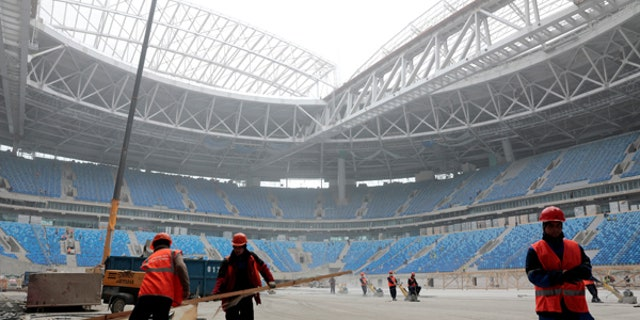 Labourers work at a new stadium under construction on Krestovsky Island, known as Zenit Arena, that will host 2017 FIFA Confederations Cup and 2018 FIFA World Cup matches, in St. Petersburg, Russia.