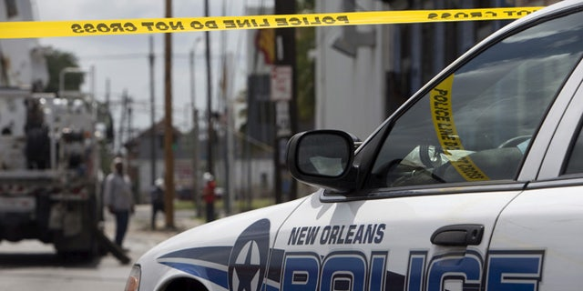 Police officers watch over the scene where New Orleans police officer Daryle Holloway was shot in New Orleans June 20, 2015. Holloway was shot and killed on Saturday while transporting a suspect to jail, and a manhunt was under way for the gunman, officials said.   REUTERS/Lee Celano - RTX1HEKE