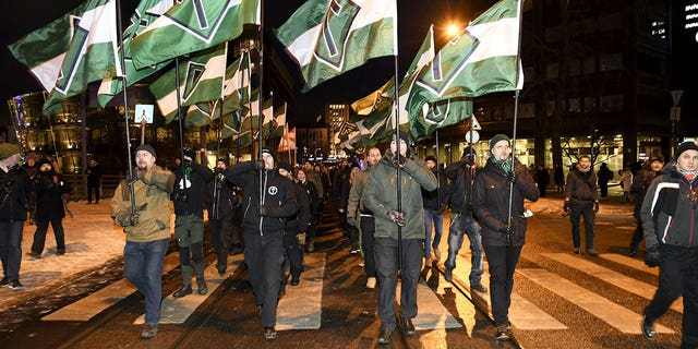 Members of the Nordic Resistance Movement are seen marching in Finland, carrying flags which prominently feature the Tyr rune.