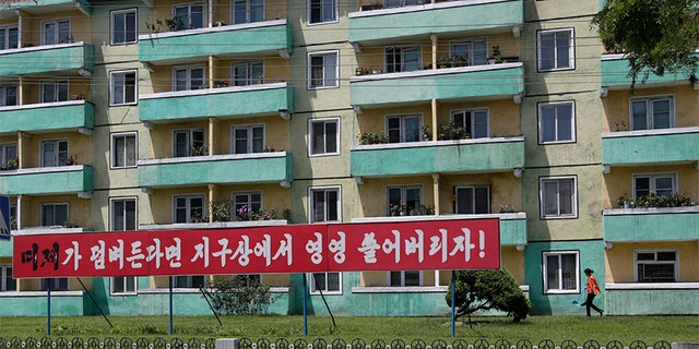 A woman walks outside an apartment building in Pyongyang where an anti-U.S. propaganda banner was put up in late June. But those who have visited the city in the wake of the Trump-Kim summit say some of that sentiment has started to disappear.