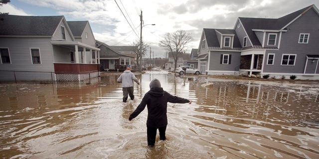 Kaylee Collin, right, and Spencer Stone walk through water along North Avenue in Camp Ellis in Saco, Maine on Sunday, March 4, 2018.