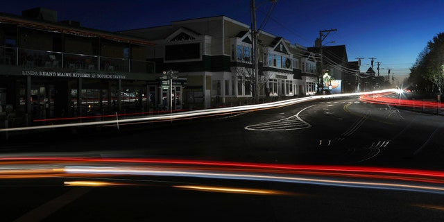Lights from automobile traffic leave trails on a street in Freeport, Maine, where most outlet shopping stores are closed after a storm knocked out electricity.