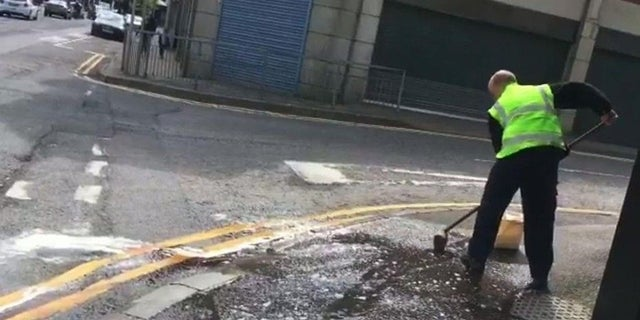 Workers clean the street after a woman was found covered in blood following an attack.