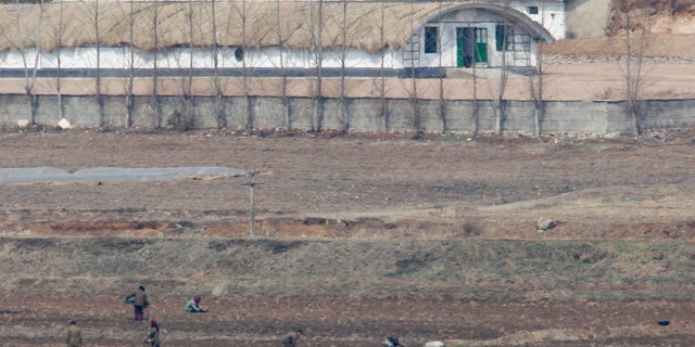 North Koreans work on a field in the propaganda village of Gijungdong near the truce village of Panmunjom in the demilitarized zone in Paju, 42 km (26 miles) northwest of Seoul, that separates North Korea from the South .