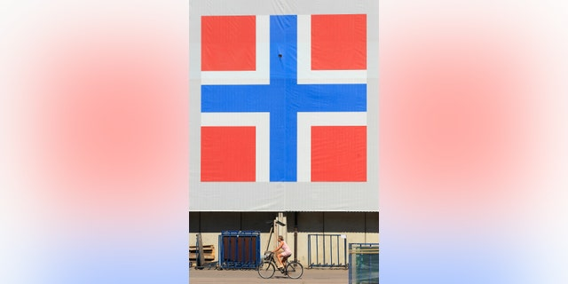 File photo - A woman cycles past a banner of the Norwegian flag attached to a warehouse in Oslo June 20, 2012. (REUTERS/Cathal McNaughton)