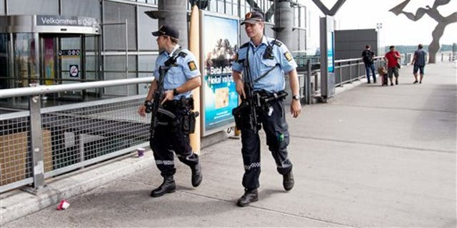 """July 24: Armed Police patrol outside the terminal building at Oslo Airport. Norway's intelligence service says it has been warned of an imminent """"concrete threat"""" against the nation from people with links to Islamic fighters in Syria."""