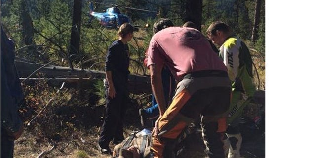Photo shows rescuers escorting injured John Sain to helicopter in Idaho woods.(Jennifer Sain)