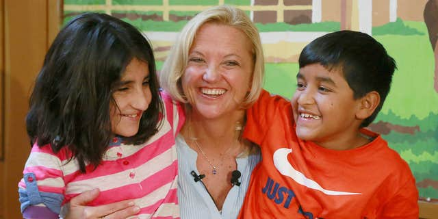 """March 27, 2015: Lynette Austin, known as """"Captain Sam,"""" poses with war victims, Shah Bibi Tarakhail, left, and Abdul Wahid, during a media event at Shriners Hospitals for Children in Los Angeles."""