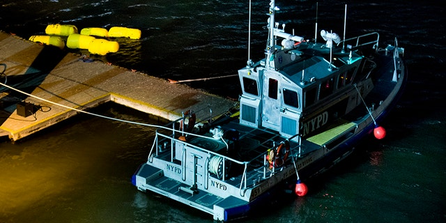 March 11, 2018: Yellow buoys that a New York police officer said are suspending a helicopter that crashed into the East River float next to a NYPD police boat at a pier in New York.