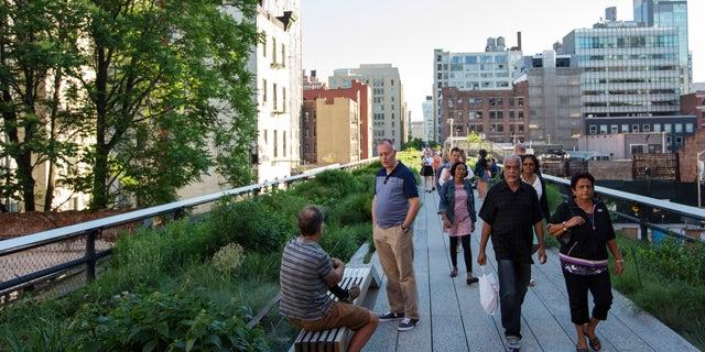 Pedestrians walks along High Line park in New York City