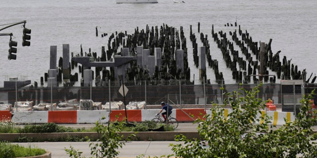 In this July 21, 2017 photo, a sailboat passes the exposed pilings of Pier 55 on the shores of the Hudson River in New York. Media Mogul Barry Diller and wife Diane von Furstenberg have pledged $200 million to transform the site a crumbling old pier into a futuristic performance venue, but the project is is running into apposition from real estate developer Douglas Durst. (AP Photo/Bebeto Matthews)