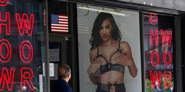 A man looks at a poster in the window of Show World Center, one of Times Square's last surviving pornography businesses.