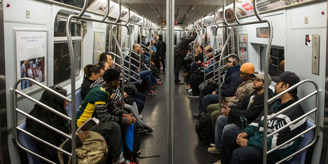 October 24, 2014 - Commuters ride a New York City L train. (REUTERS) Commuters