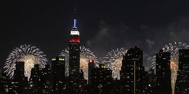 July 4: The Empire State Building, illuminated with red, white and blue lights, is seen from across the East River in the Queens borough of New York, and is backlit by fireworks exploding over the Hudson River during the Macy's Fourth of July fireworks show.