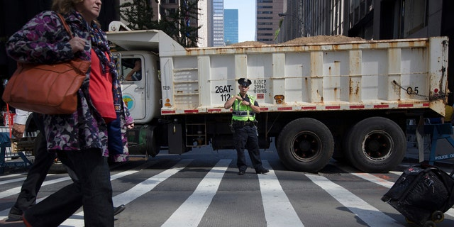 In this Sept. 24, 2015 file photo, a police office stands guard at a loaded dump truck that serves as a barricade along the perimeter of St. Patrick's Cathedral before the arrival of Pope Francis in New York.