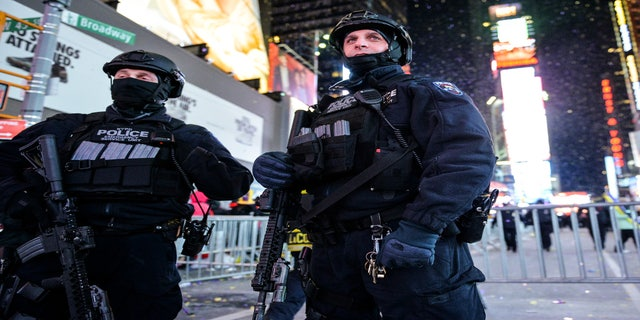 New York City Police Emergency Service Unit officers stand on guard in Times Square during New Year's Eve celebrations, Dec. 31, 2017.