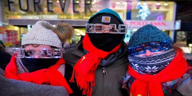 New Year's Eve revelers at Times Square in New York City dressed appropriately. From left are Elena Bardunniotis, Dominic Manshadi and Sarah Thompson, of Long Beach, Calif.