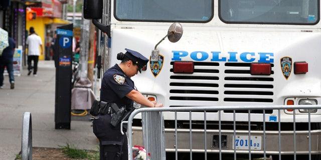 A police officer works near the site where an officer was killed in the Bronx section of New York, Thursday, July 6, 2017.  Police officer Miosotis Familia was shot to death early Wednesday, ambushed inside her command post by an ex-convict, authorities said. He was later killed after pulling a gun on police. (AP Photo/Seth Wenig)