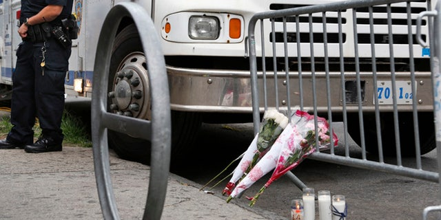 A police officer stands near the site where an officer was killed, and flowers have been left, in the Bronx section of New York, Thursday, July 6, 2017. Police officer Miosotis Familia was shot to death early Wednesday, ambushed inside her command post by an ex-convict, authorities said. He was later killed after pulling a gun on police. (AP Photo/Seth Wenig)