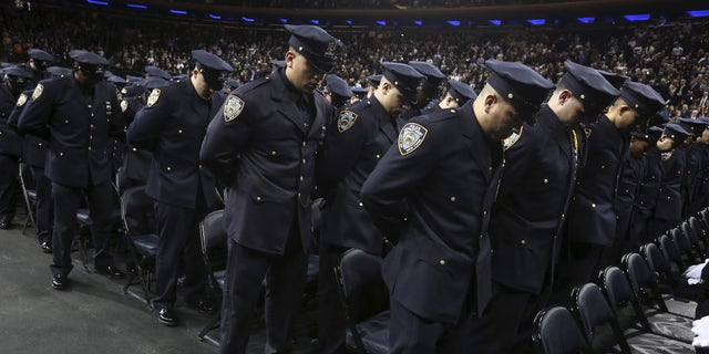 Dec. 29, 2015- Newly inducted New York Police officers observe a solemn moment at a graduation ceremony at Madison Square Garden. (REUTERS)