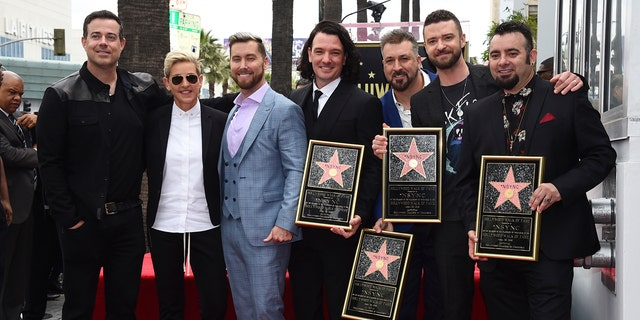 Carson Daly and Ellen DeGeneres pose with the band during their star ceremony.