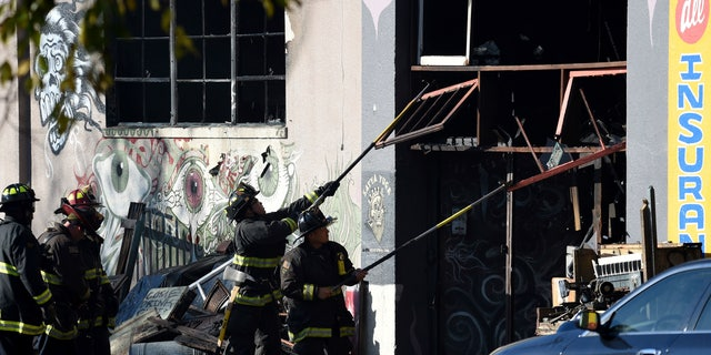 Firefighters clear an entry to a smoldering building after a fire tore through a warehouse party early Saturday, Dec. 3, 2016 in Oakland.