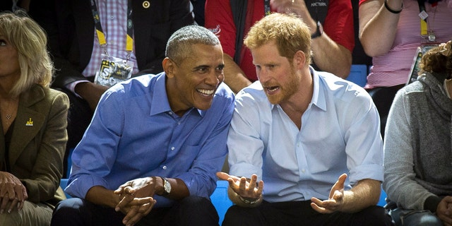 In this Friday, Sept. 29, 2017 file photo, former U.S. President Barack Obama, center left, and Britain's Prince Harry watch wheelchair basketball at the Invictus Games in Toronto.