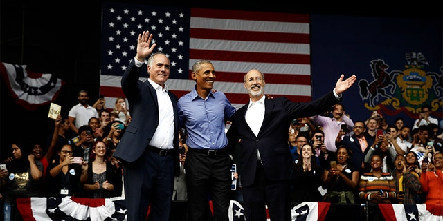 Former President Barack Obama stands with Sen. Bob Casey D-Pa., left, and Gov. Tom Wolf, during a campaign rally in Philadelphia on Friday.