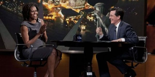 April 11, 2012: In this photo provided by Comedy Central, first lady Michelle Obama laughs with Stephen Colbert during her appearance on The Colbert Report.
