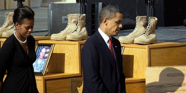President Obama and first lady Michelle Obama walk past a memorial for victims of the Fort Hood shooting Nov. 10 at Fort Hood, Texas. (AP Photo)