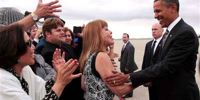 President Obama stops to greet people on the tarmac during his arrival at Moffett Airfield, near San Jose, Calif., Sept. 25.