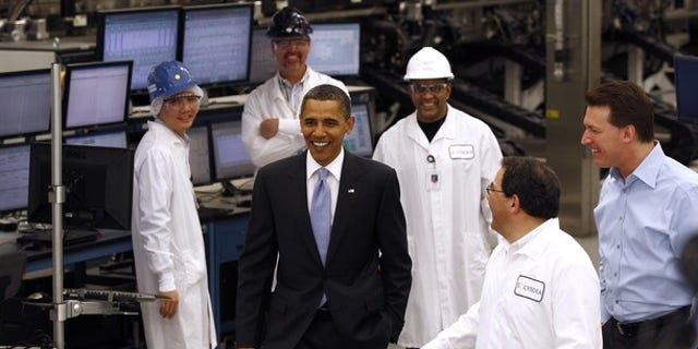 President Barack Obama (C) talks with workers as he tours Solyndra, Inc. , a solar panel manufacturing facility in Fremont, California, in this May 26, 2010 file photo.