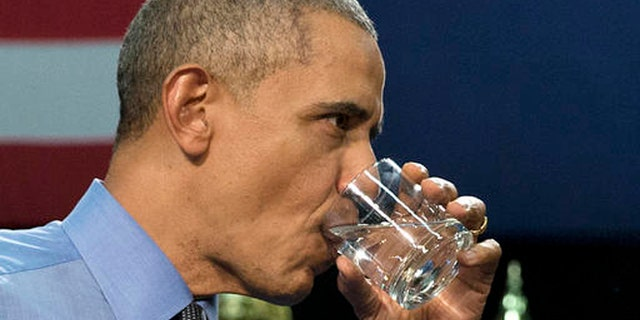 President Barack Obama drinks water as he finishes speaking at Flint Northwestern High School in Flint, Mich., Wednesday, May 4, 2016, about the ongoing water crisis.