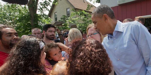 June 26, 2014: President Barack Obama greets a small child on the sidewalk outside of Matt's Bar in Minneapolis.