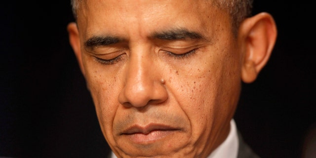 Feb. 6, 2014: President Barack Obama closes his eyes as a prayer is offered at the National Prayer Breakfast in Washington. The president told the non-denominational gathering of political leaders that freedom of religion across the world is important to national security and is a central tenet of U.S. diplomacy.  (AP/Charles Dharapak)