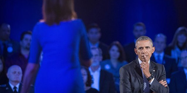 President Barack Obama, right, listens to a question from Taya Kyle, left, widow of U.S. Navy SEAL Chris Kyle, during a CNN televised town hall meeting hosted by Anderson Cooper at George Mason University in Fairfax, Va., Thursday, Jan. 7, 2016. (AP)