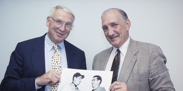 FILE - In this June 6, 1991, file photo, former New York Giants baseball player Bobby Thomson, left, poses with former Brooklyn Dodgers pitcher Ralph Branca holding a photo showing Branca, right, and Thomson fooling around before a World Series baseball game at Yankee Stadium on Oct. 10, 1951.