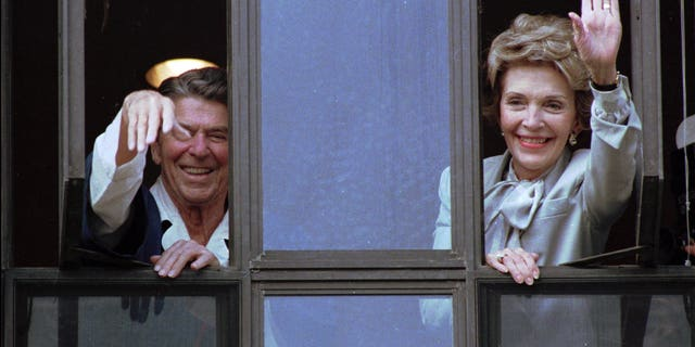 July 18, 1985: President Ronald Reagan and Nancy Reagan wave from the windows of his hospital room at the Navy Medical Center.