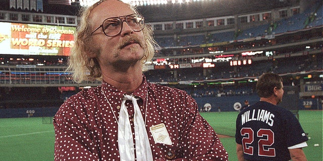 """Oct. 23, 1992:  Canadian author W.P. Kinsella stands on the field before game five of the World Series between the Toronto Blue Jays and Atlanta Braves at SkyDome in Toronto, Ontario. Kinsella, the author of """"Shoeless Joe,"""" the award-winning novel that became the film """"Field of Dreams,"""" has died at 81."""